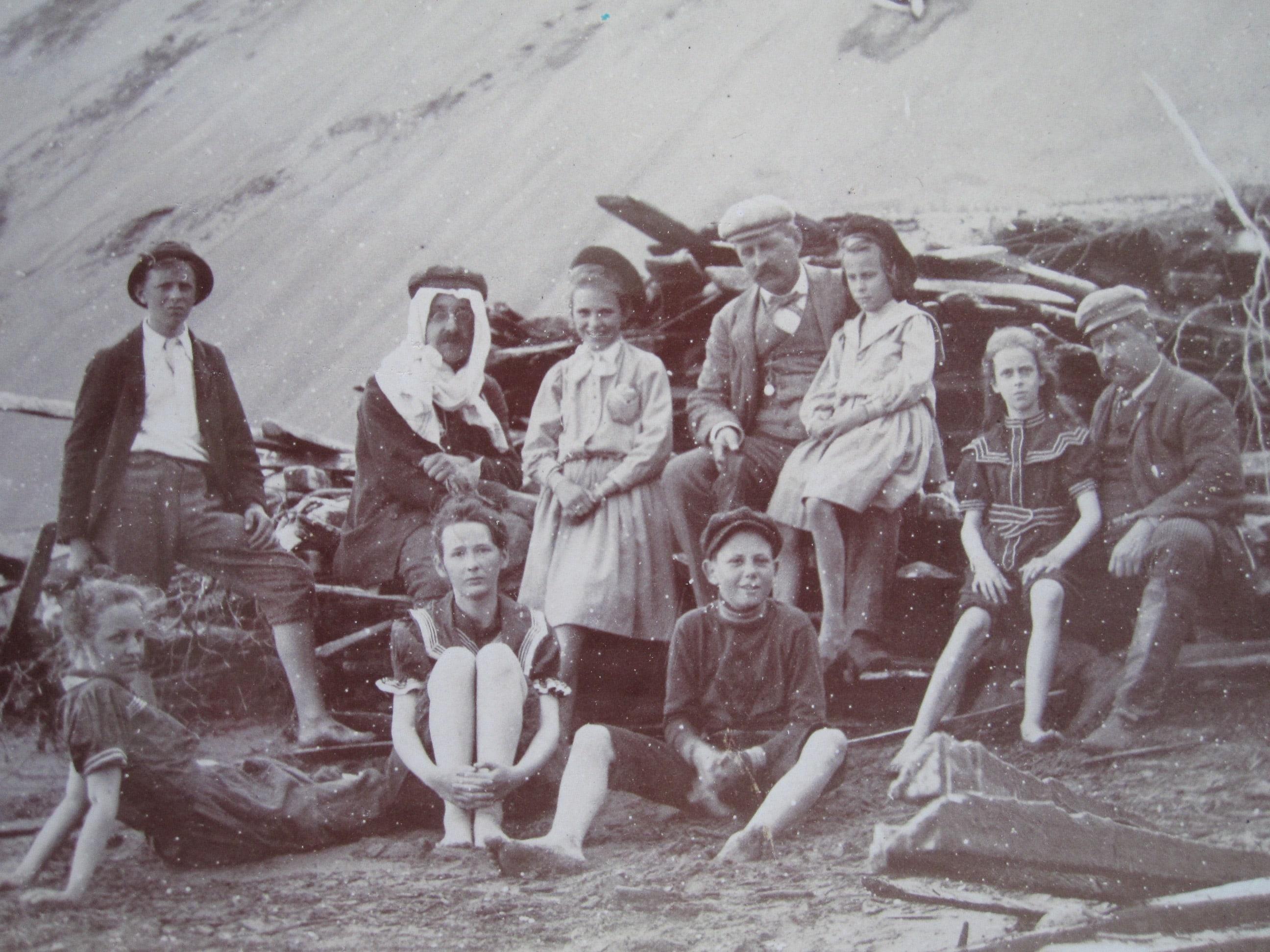 Dix personnes posent au pied de dunes de sable, assis près d'un amoncellement de morceaux de bois.