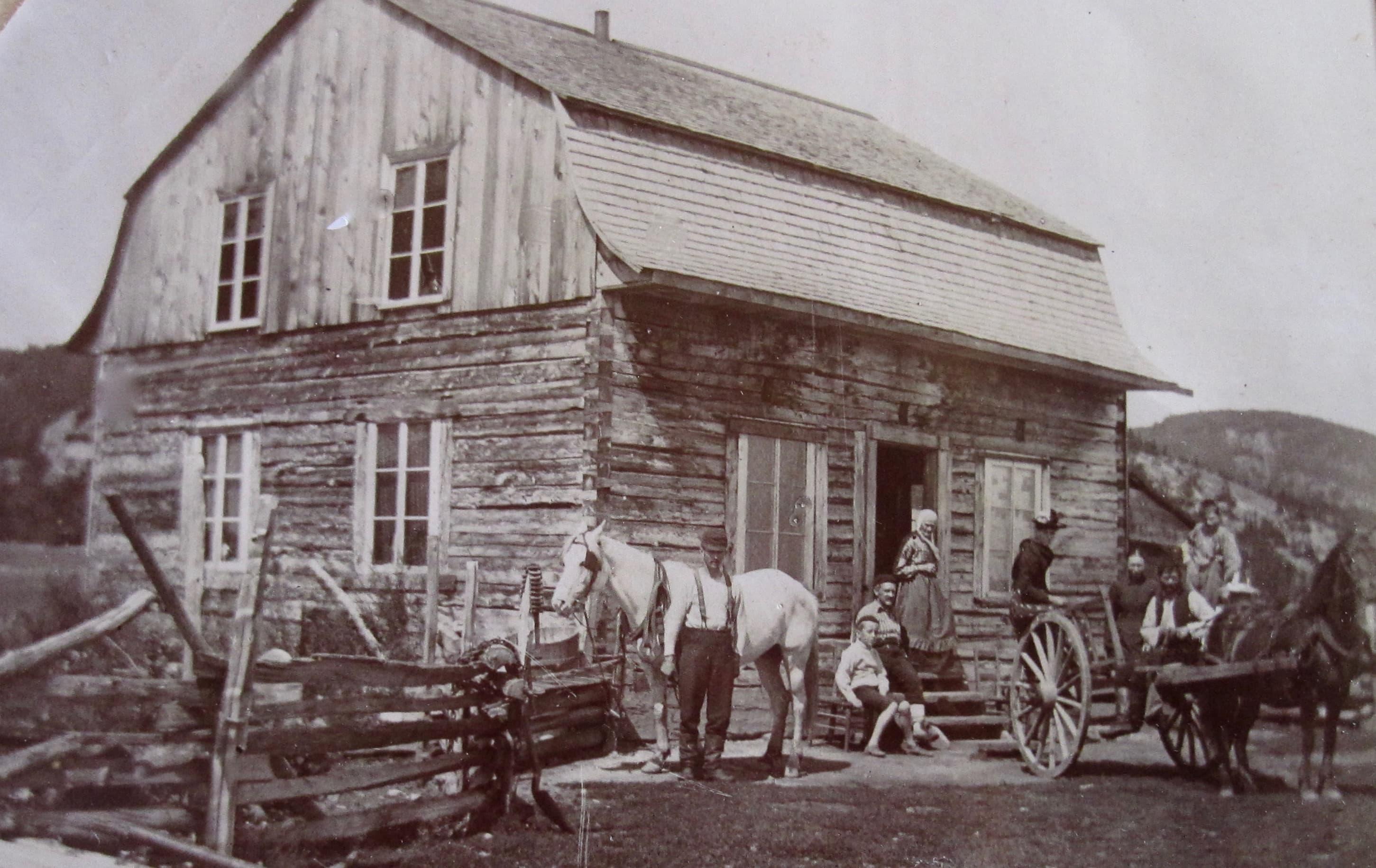Quelques personnes posent devant une maison d'habitant construite en pièces sur pièces. Deux chevaux sont au repos.