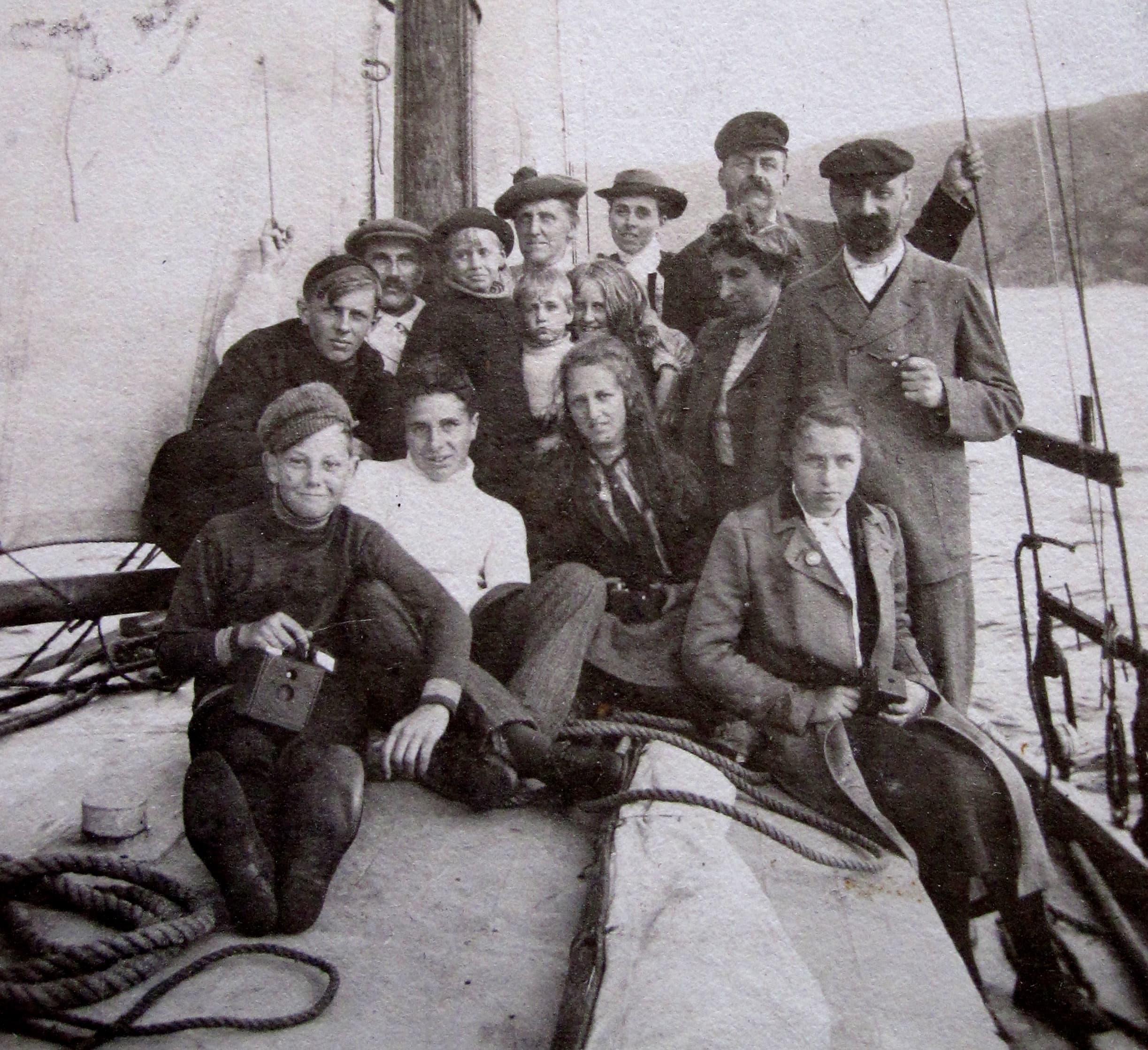Un groupe de vacanciers pose sur le pont d'un petit bateau.