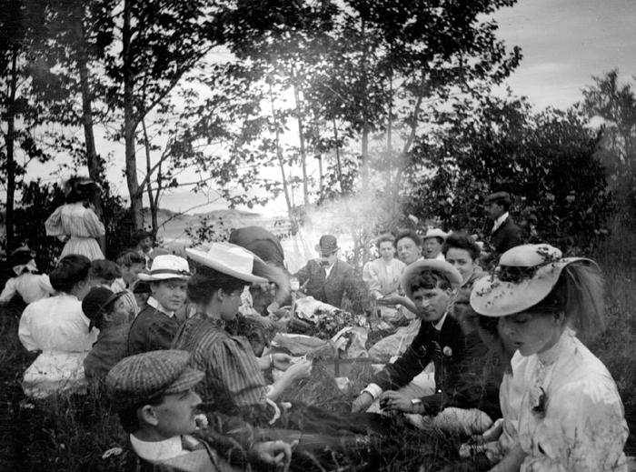 Des personnes sont assises dans l'herbe à l'occasion d'un pique-nique.
