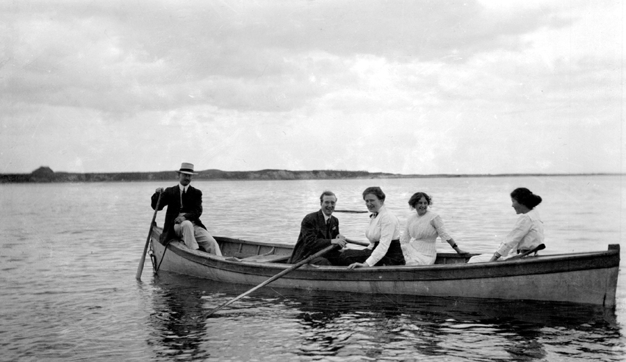 Un petit groupe de personnes se trouvent dans une chaloupe flottant sur l'eau.