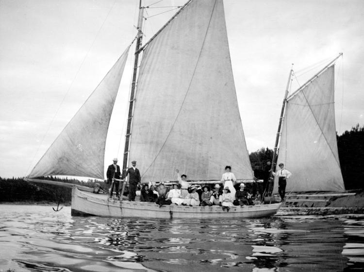 Un bateau à voiles flotte sur l'eau, rempli de passagers.