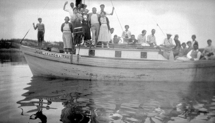 Des personnes vêtues assez simplement sont à bord d'un petit bateau.