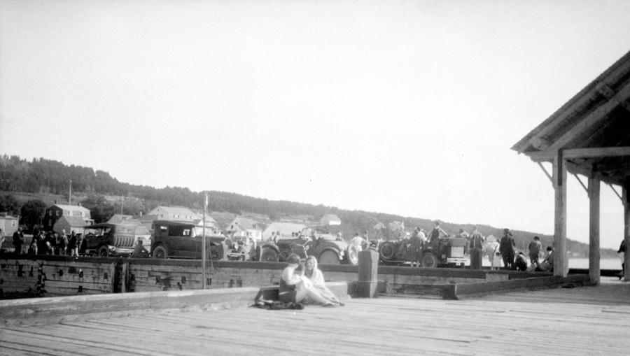 Deux jeunes filles discutent sur un quai animé; en arrière-plan, plusieurs voitures sont stationnées.