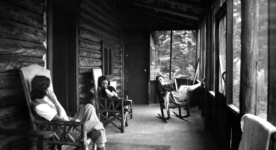 Trois jeunes femmes se bercent dans la véranda d'un chalet en bois rond.