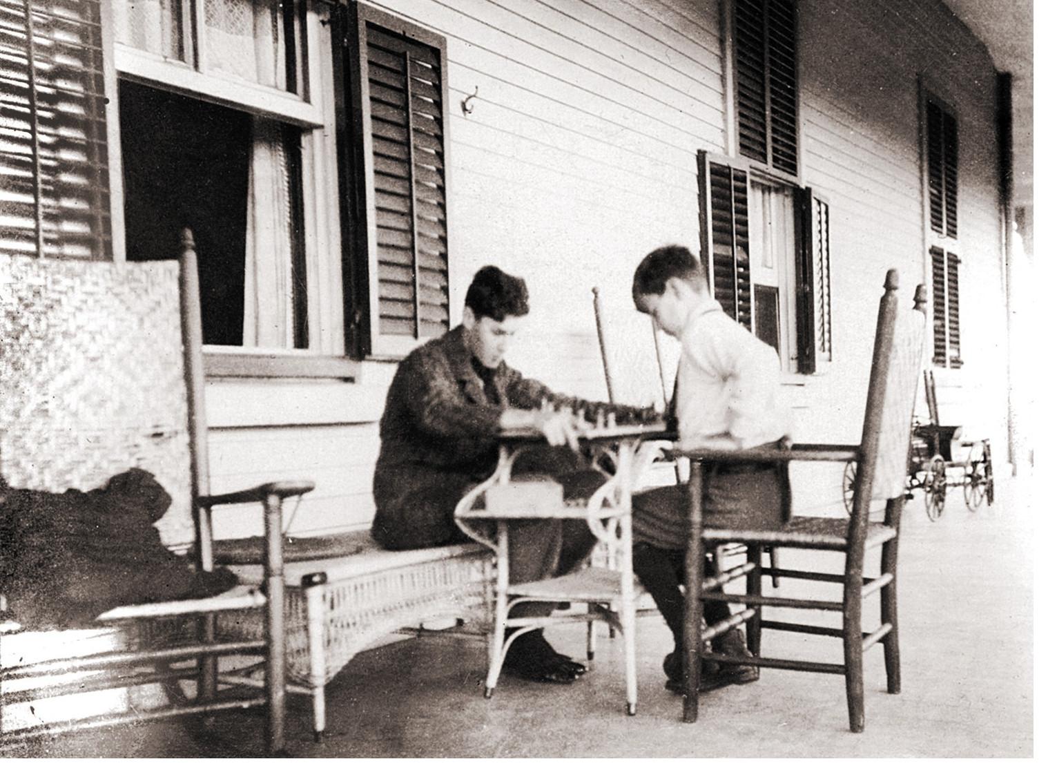 Deux jeunes adolescents bien mis jouent aux échecs sur une véranda.
