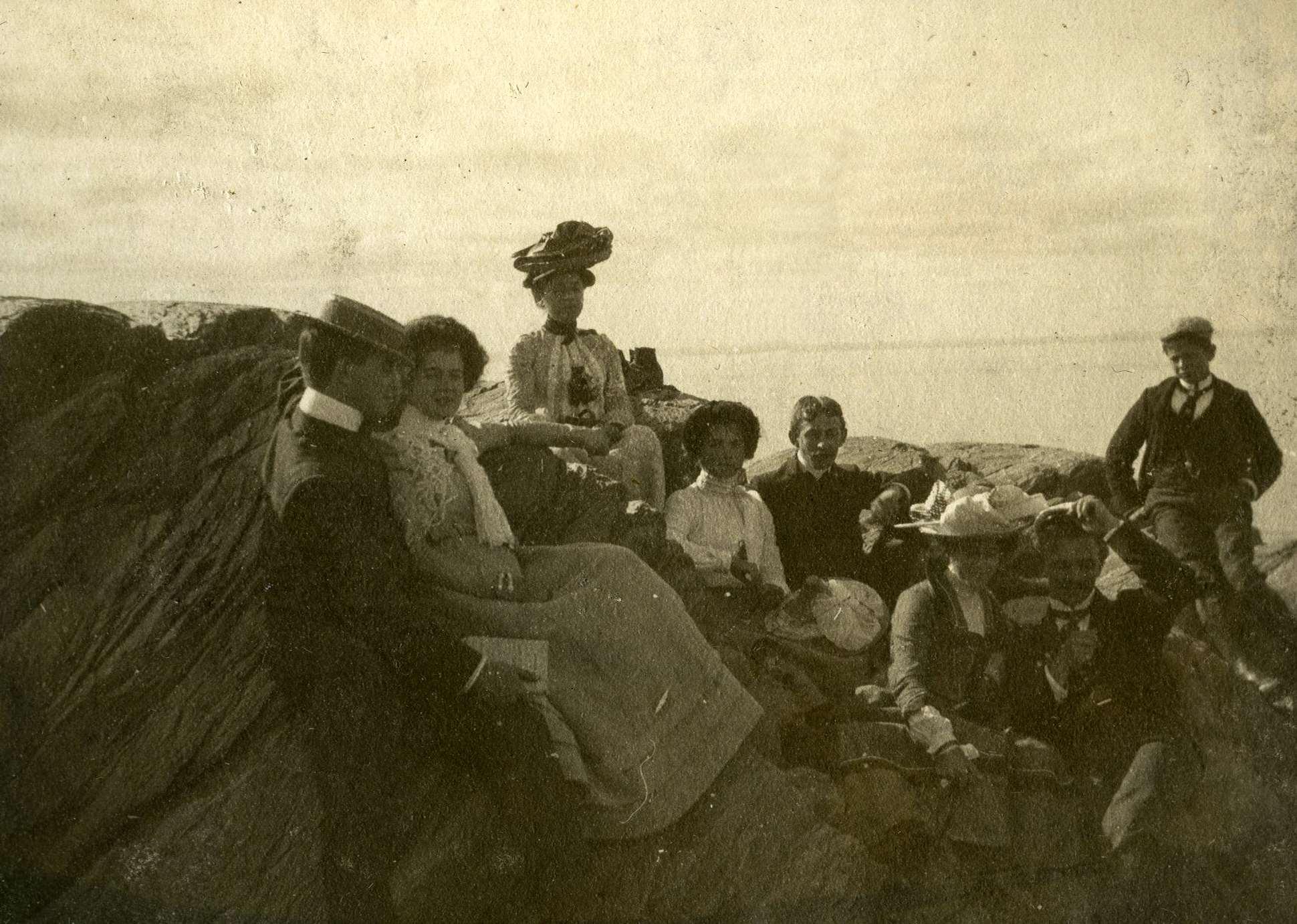 Trois couples de jeunes gens sont assis sur les rochers au bord de l'eau, accompagnés d'une femme et d'un jeune homme.