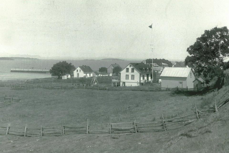 Petit champ en avant-plan, avec le fleuve, un quai, quelques maisons et bâtiments en arrière-plan.