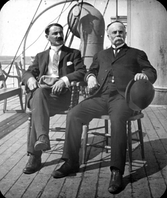 Deux hommes sont assis sur des chaises sur le pont d'un bateau.
