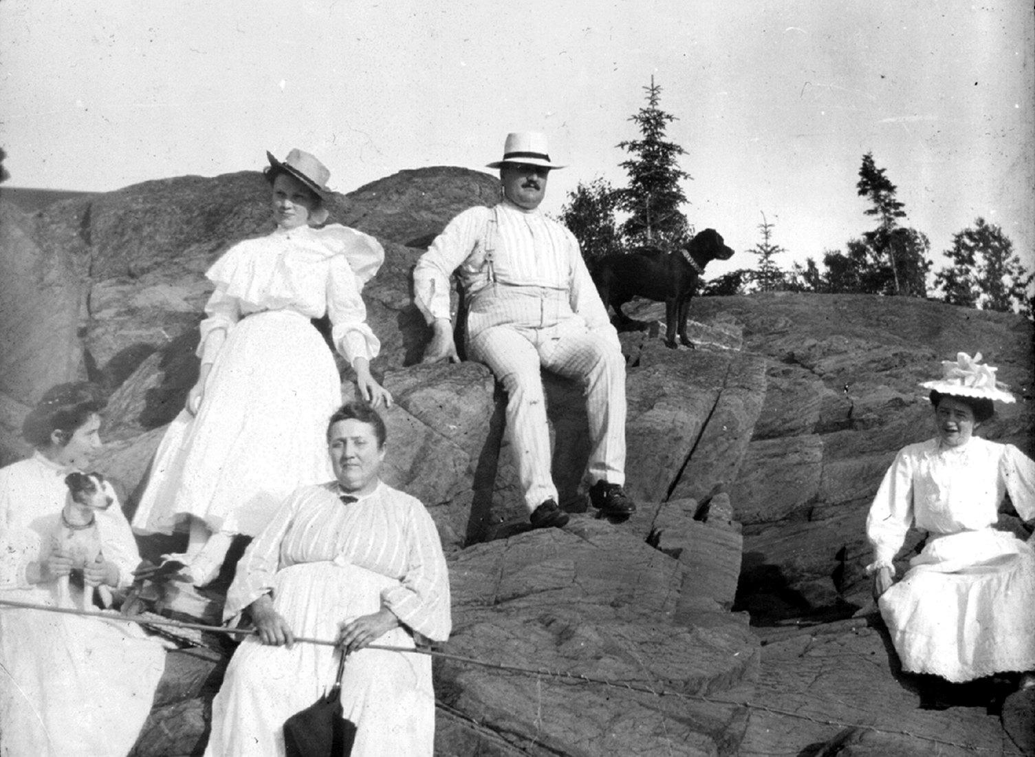 Cinq adultes vêtus de blanc, accompagnés de deux chiens, sont assis sur un rocher. Une femme tient une canne à pêche.