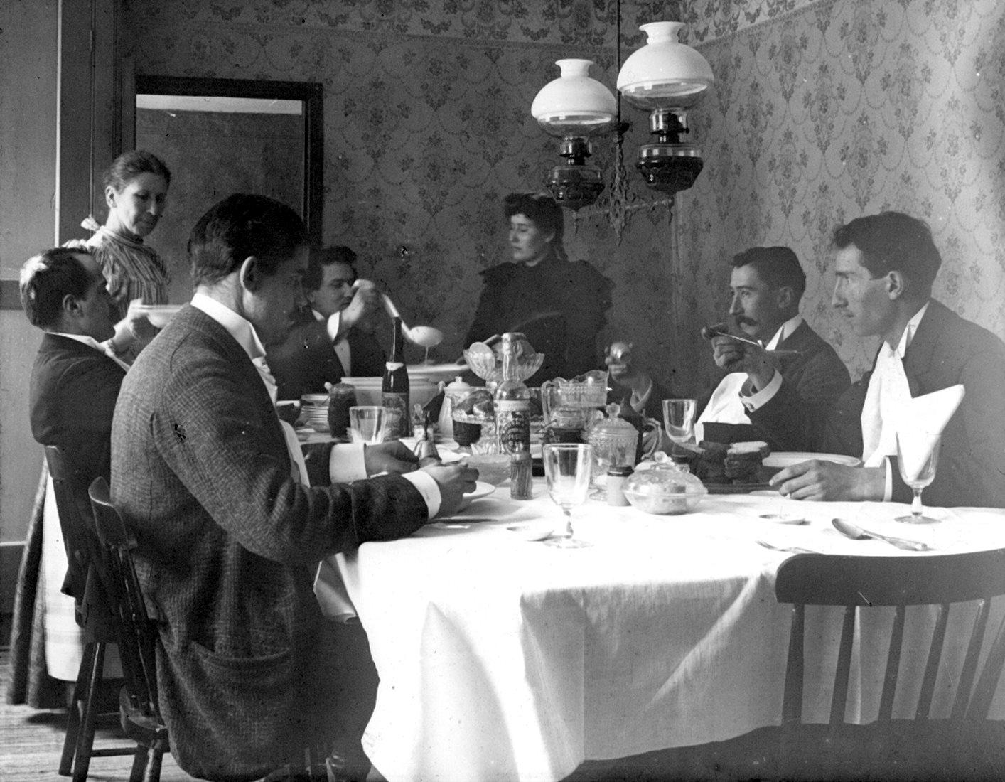 Un groupe est attablé à une table bien garnie, alors qu'une femme fait le service.