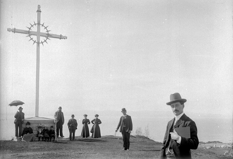 A group gathered at the foot of a wayside cross in Saint-Denis-De La Bouteillerie.
