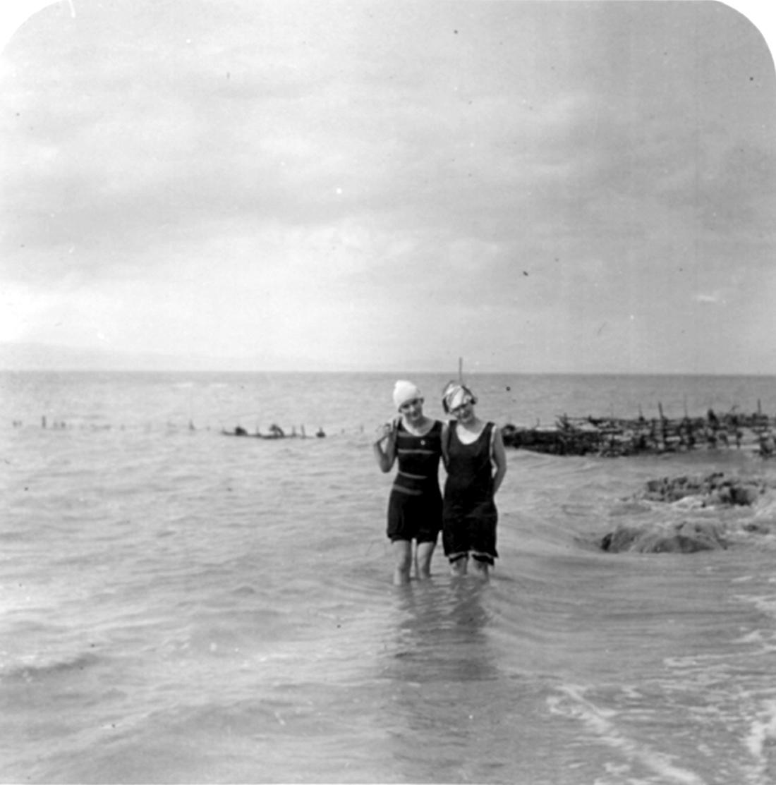 Deux jeunes femmes se baignent jusqu'aux genoux dans un grand cours d'eau, près d'une pêche à fascine.