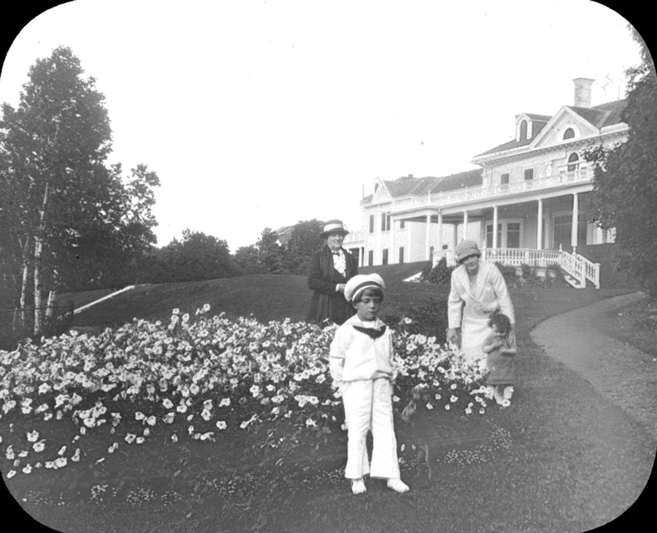 Deux femmes et deux enfants posent près d'un parterre de fleurs, devant une résidence très cossue.