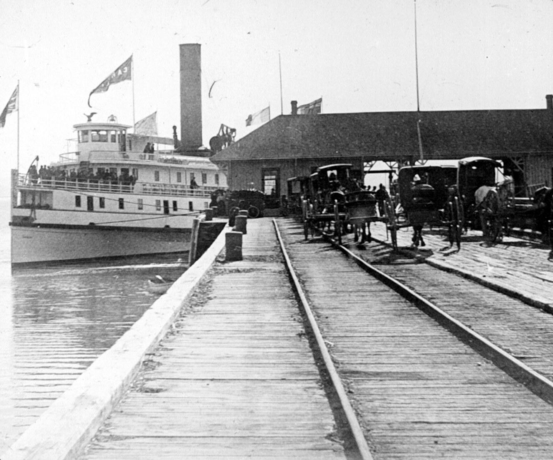 Un bateau à vapeur accosté à un quai, qui comporte une voie ferrée. Des charretiers attendent la descente des passagers.