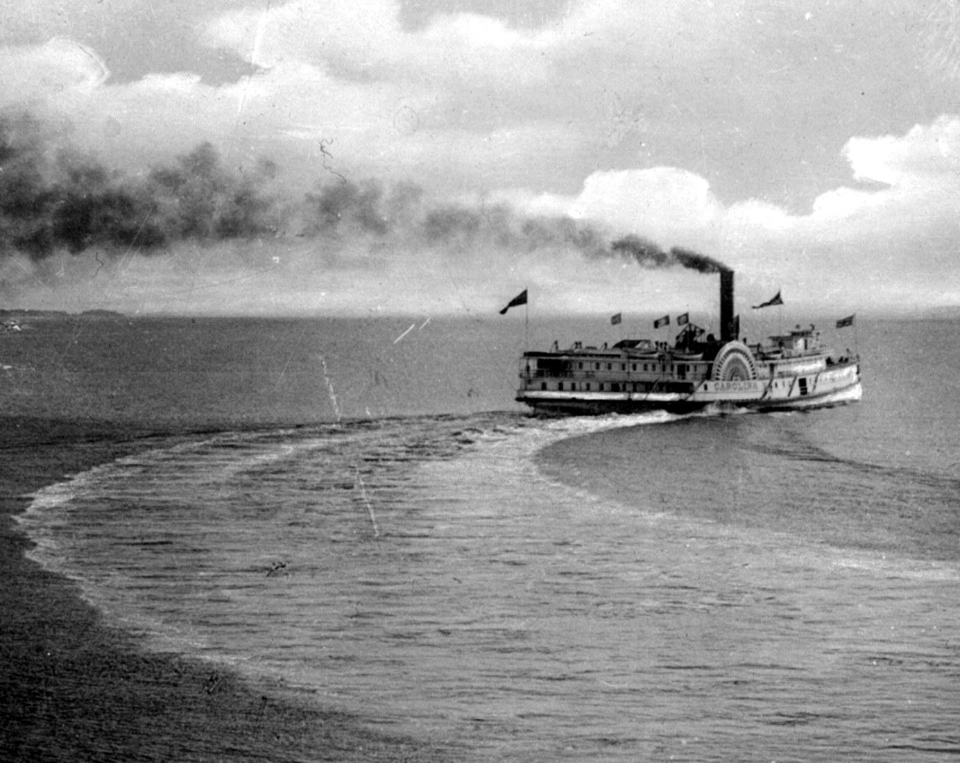 Un navire de croisière effectue une manœuvre. Une fumée noire s'échappe de sa cheminée.