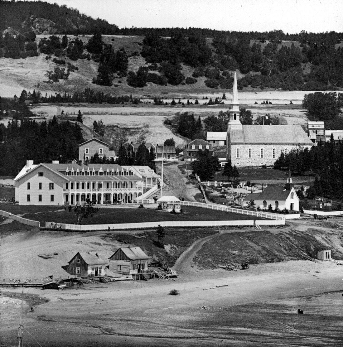 Un petit hameau où se trouvent un grand hôtel, une chapelle et une église en pierre près d'une plage en contrebas.