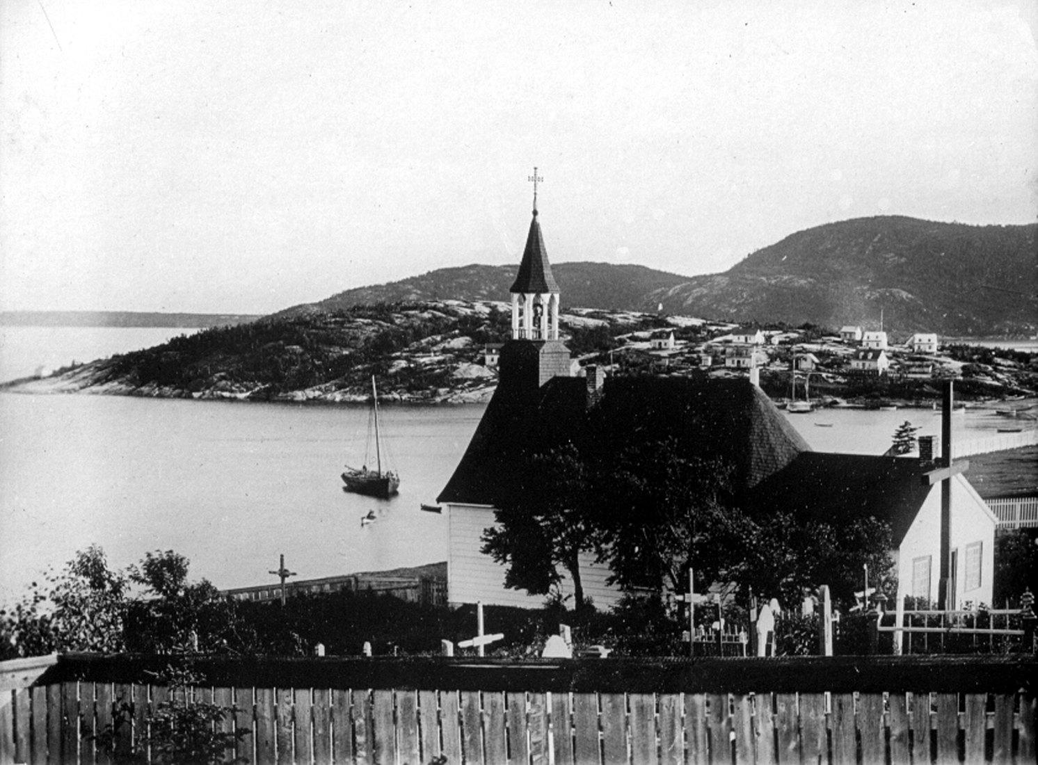 Une chapelle et son cimetière surplombent une baie, où sont amarrées des embarcations, dont deux bateaux à voile.
