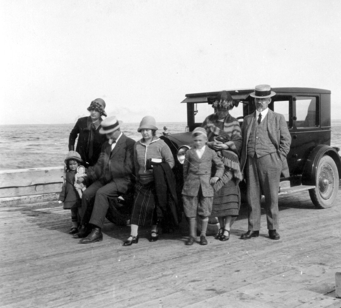 Five adults and two children on vacation, posing in front of an old car parked on a wharf.