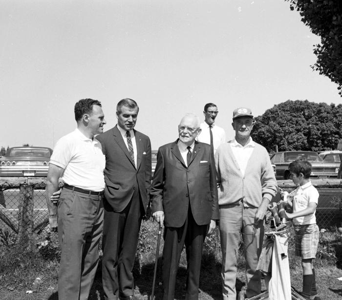 Portrait d'un groupe de quatre hommes accompagnés d'un caddie soutenant un sac de golf, devant un stationnement.