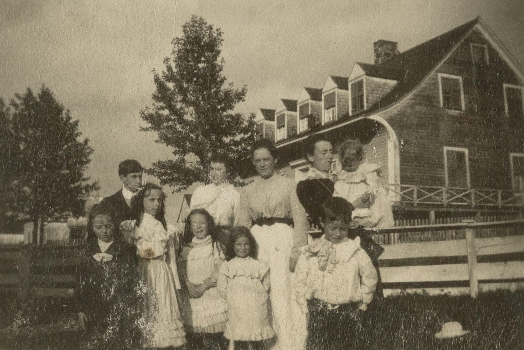 Trois femmes et plusieurs enfants posent devant une grande maison ancienne recouverte de bardeaux de cèdre.
