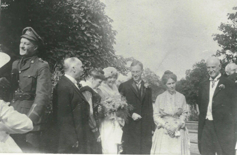 Deux nouveaux mariés sont photographiés à l'extérieur, accompagnés de leurs parents.