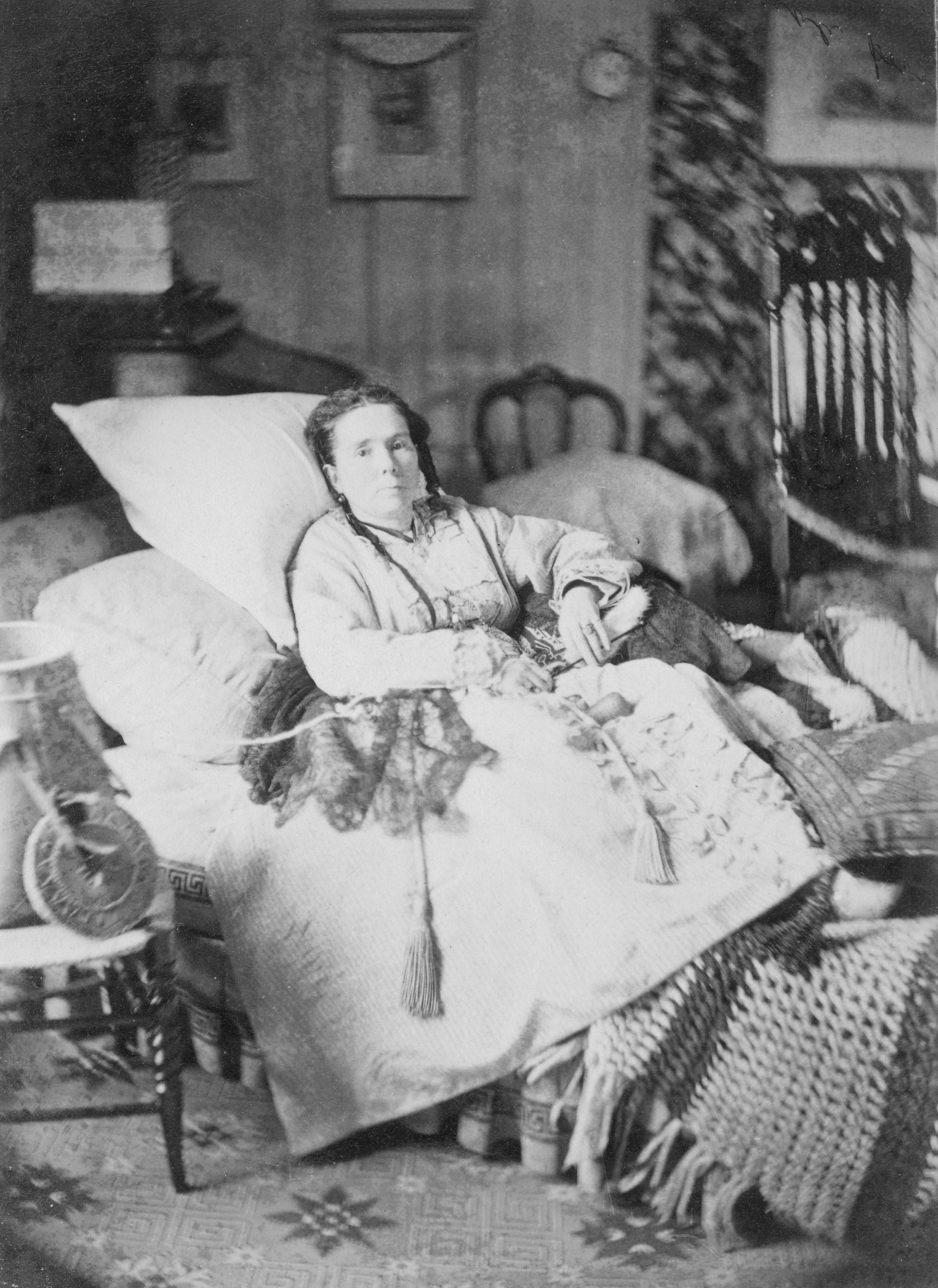 Black and white photograph of a sick women resting on a very comfortable bed.
