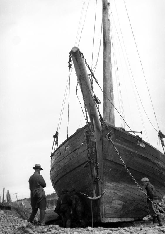 Two men observing a schooner on the shore.