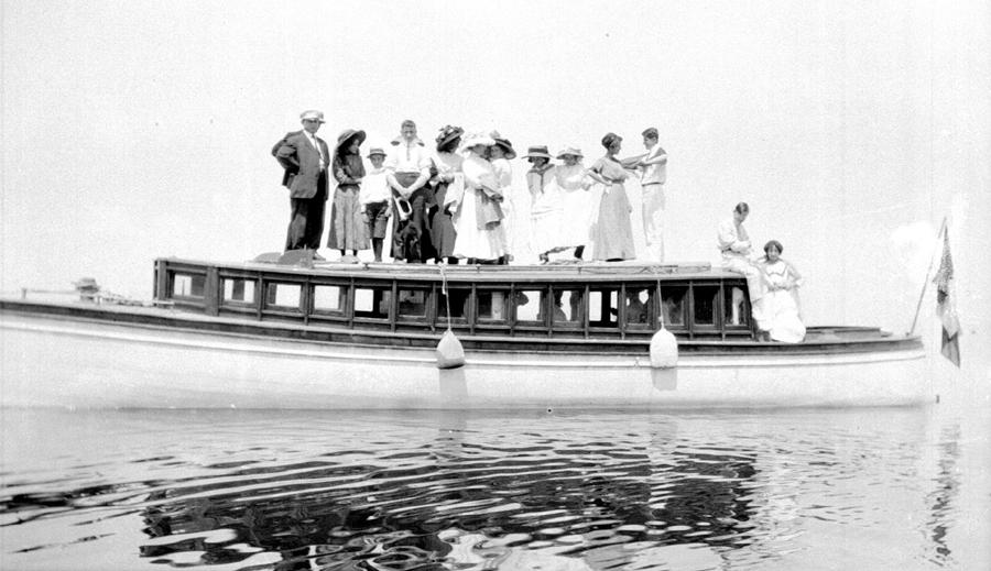 Une dizaine de personnes posent sur le toit d'un yacht motorisé.