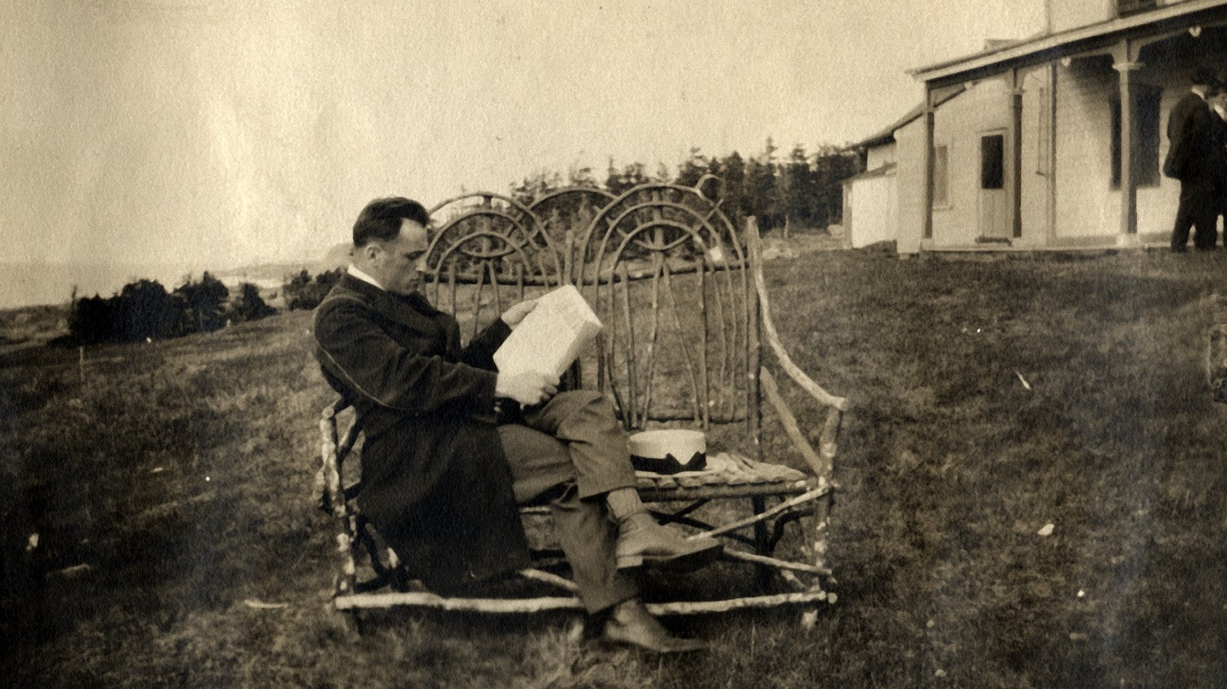 A man on vacation is reading, sitting on a wicker bench at the rear of a summer residence.