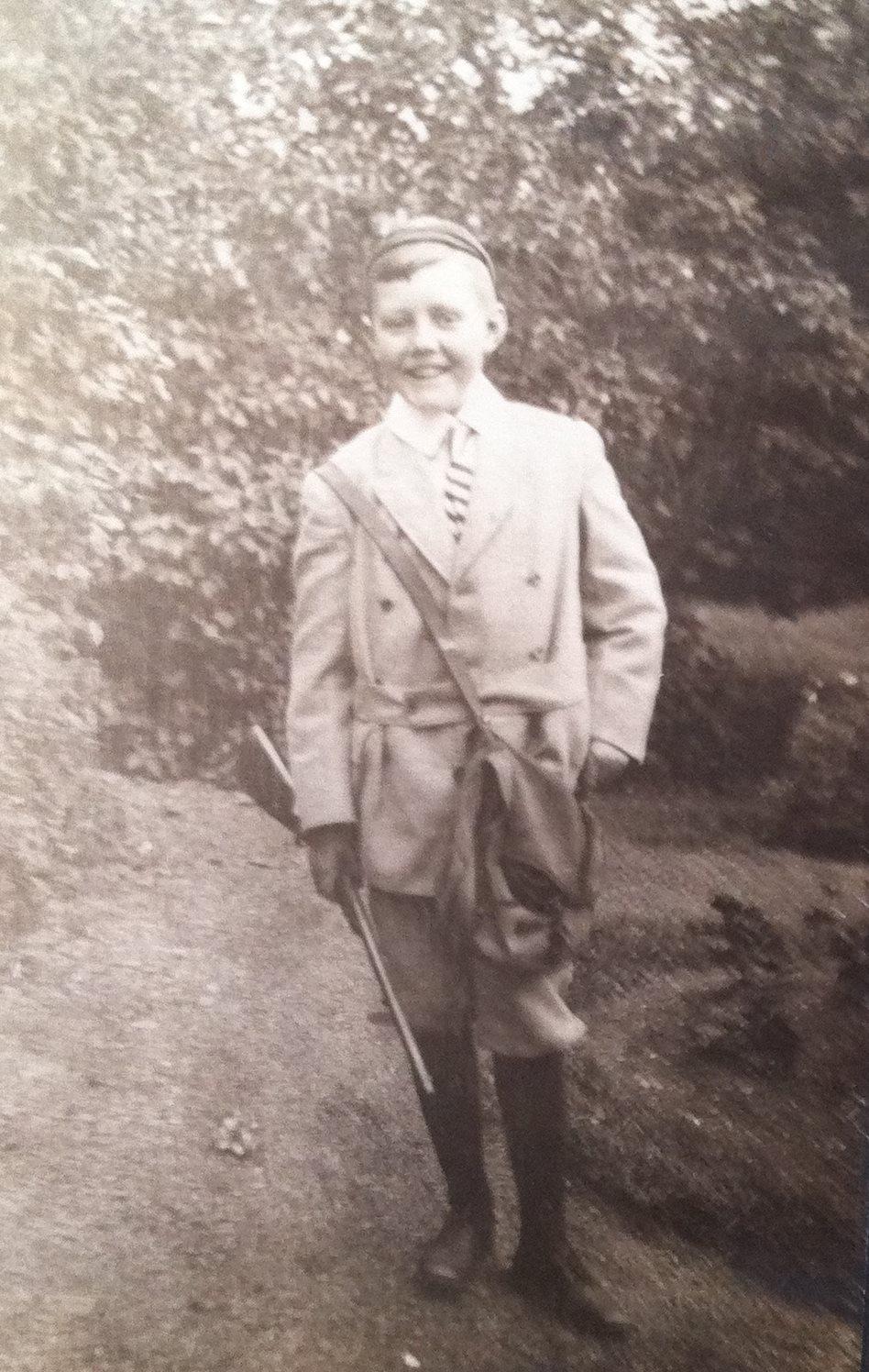 Un enfant pose fièrement en habit de chasse très stylé, carabine à la main.