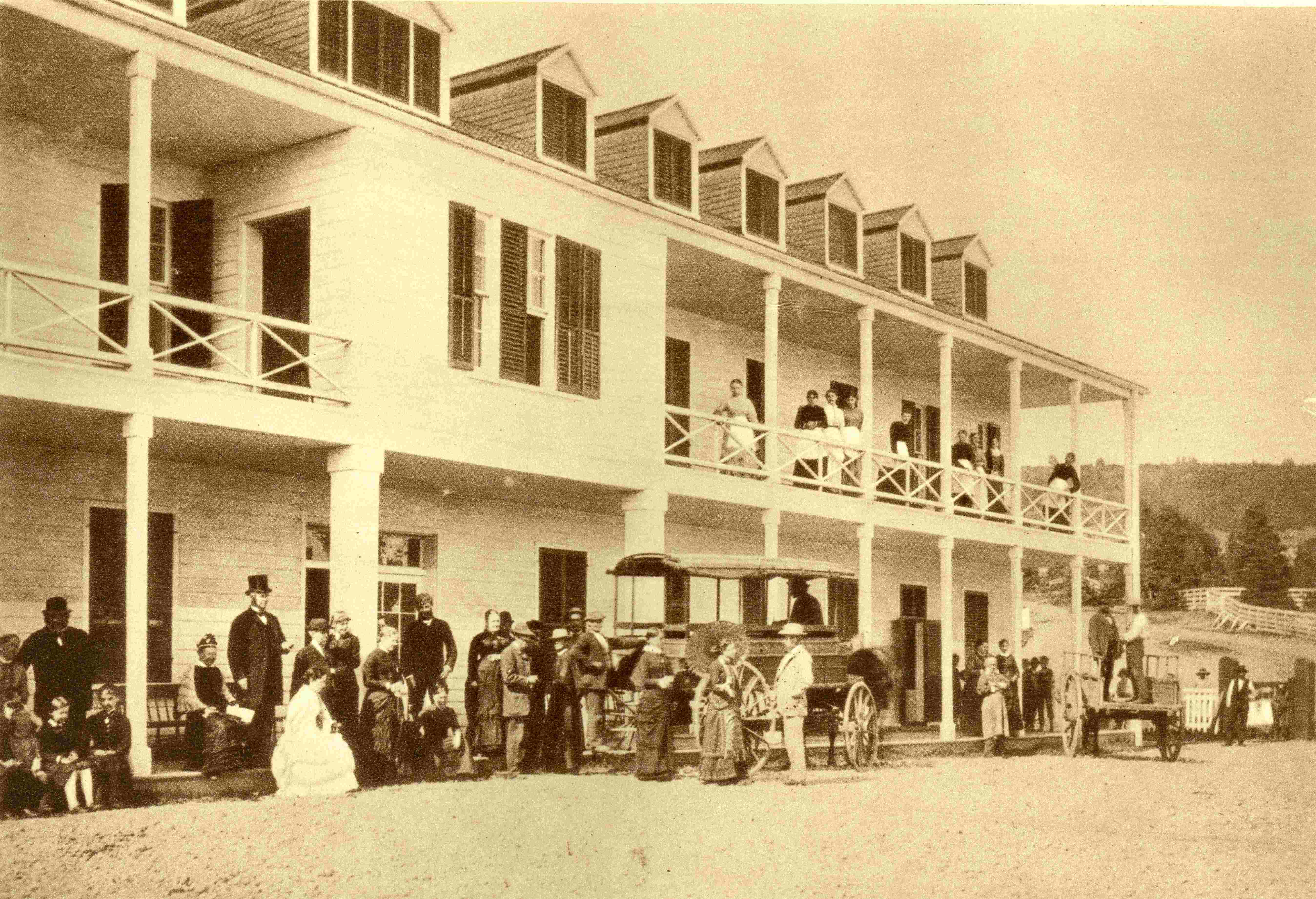 Clients milling in front of a hotel and a horse-drawn omnibus for transporting passengers.