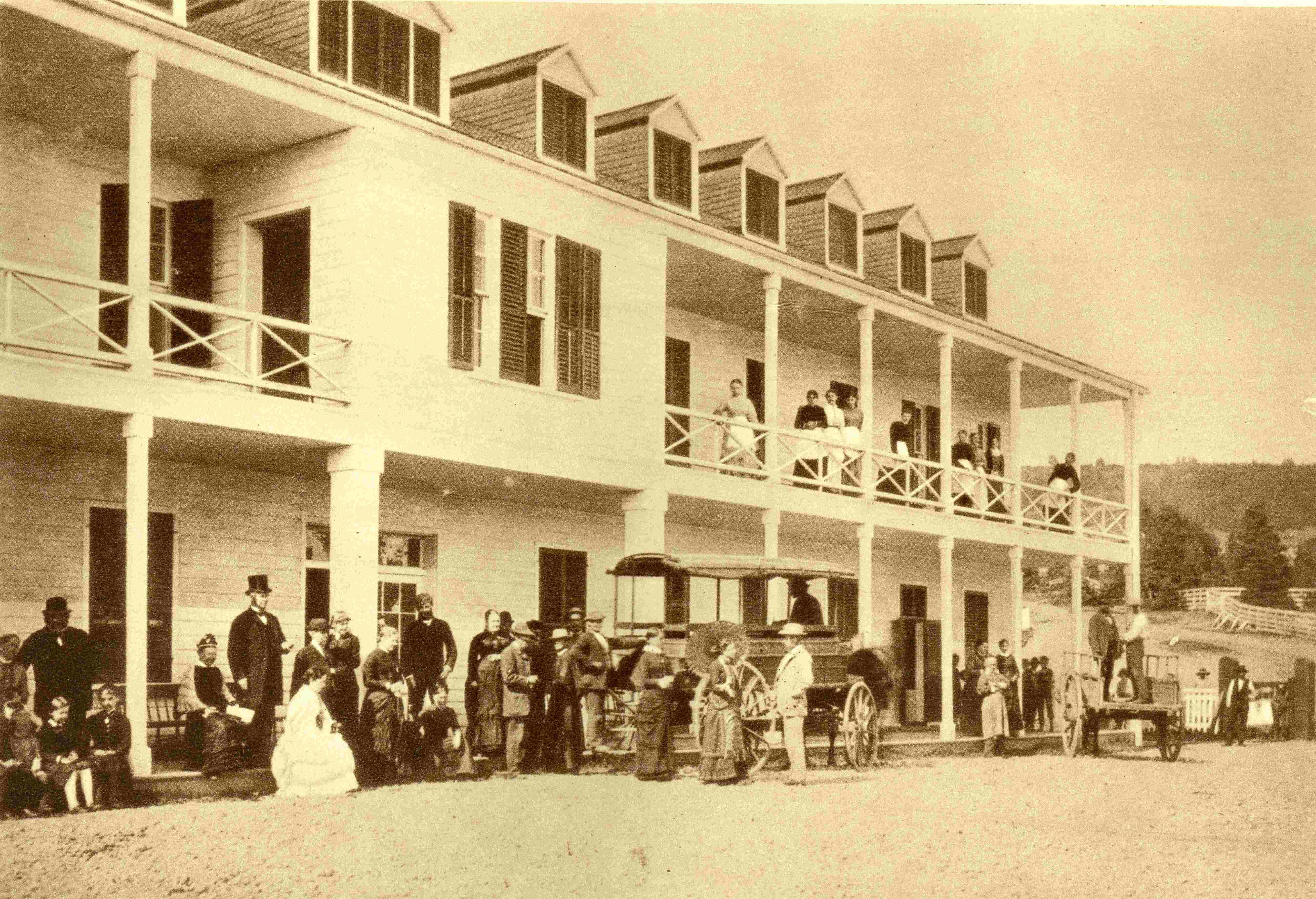 Plusieurs clients se tiennent devant un hôtel. On aperçoit une voiture à cheval destinée au transport des passagers.