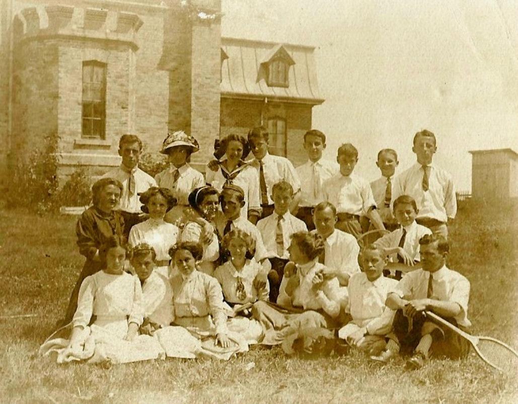 Une vingtaine de jeunes bien vêtus posent devant un bâtiment ressemblant à un château. Certains tiennent une raquette de tennis.