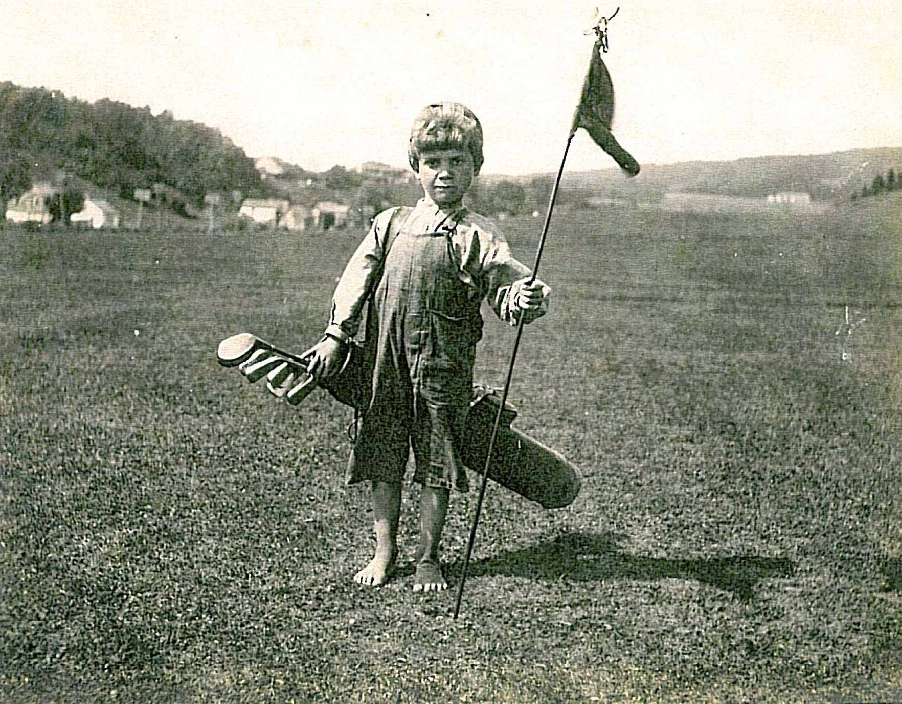 A barefoot child caddie, carrying a golf bag and holding a flag.