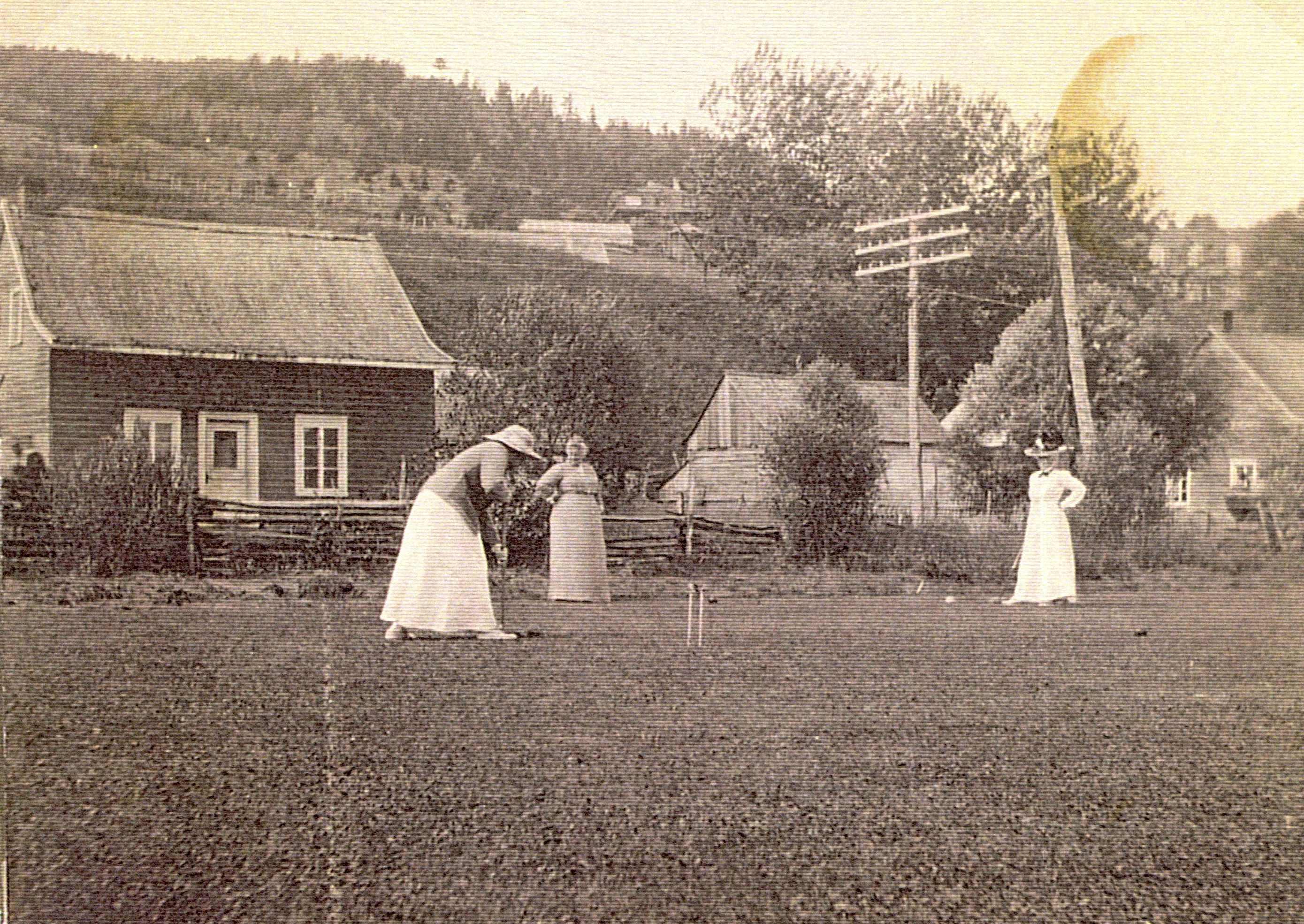 Trois femmes jouent au croquet près de maisons situées au pied d'une montagne.