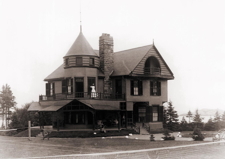 Deux villégiatrices sont photographiées sur la galerie d'une imposante villa, alors qu'une domestique ouvre les volets.