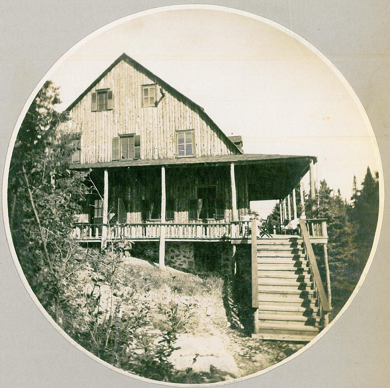 Grande résidence au revêtement extérieur en planches, construite au flanc d'un rocher et ceinturée par une galerie couverte.