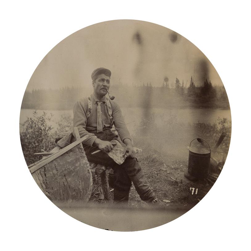 Un homme fumant la pipe est assis près d'un canot, avec un lac sauvage en arrière-plan.