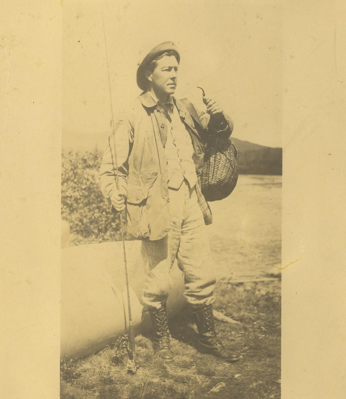 Photographie sur papier jauni d'un pêcheur et son équipement, dont une canne à pêche, un canot et panier à poissons en osier.