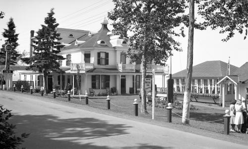 black and white photograph of an inn and a pavilion with many windows