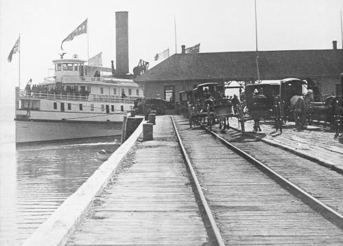 A steamboat at a wharf equipped with rails and porters waiting for passengers to land.