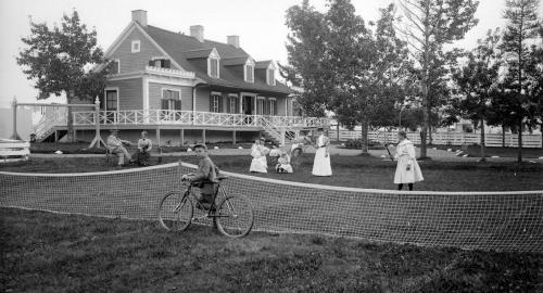 A family enjoys the summer, behind an opulent house. A child rides a bike, others play tennis or chat.