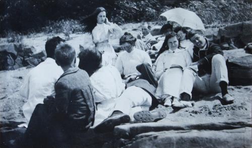 Une dizaine d'adolescents, portant de vêtements longs et propres, se reposent sur une plage.