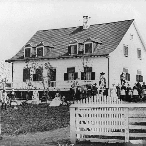 A group of fifteen people posing in front of an old country home.