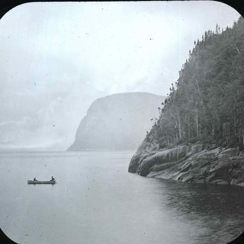 Two canoers fishingat the foot of a cliff that plunges into a very wide river.