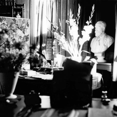 A black and white photograph of an office heavily decorated with knickknacks and flowers.