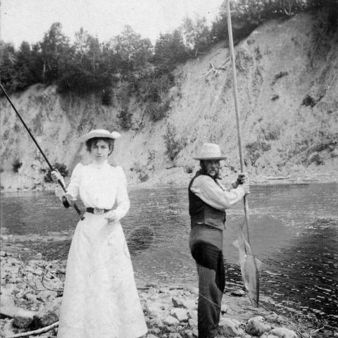 Une femme à la taille très fine tient une canne à pêche, à côté d'un guide qui tient un filet de pêche.