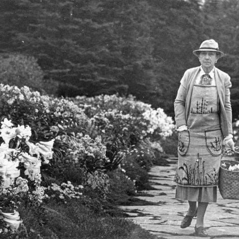 A distinguished woman wearing an embroidered apron and walking along a flower-lined walkway, basket in hand.