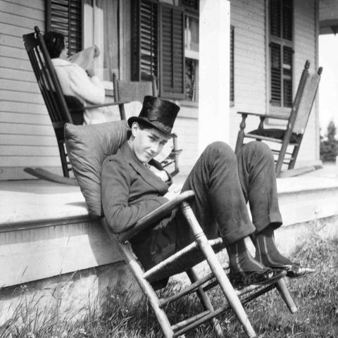 A young man wearing a top hat and sitting nonchalantly on a chair, while a woman reads in the background.